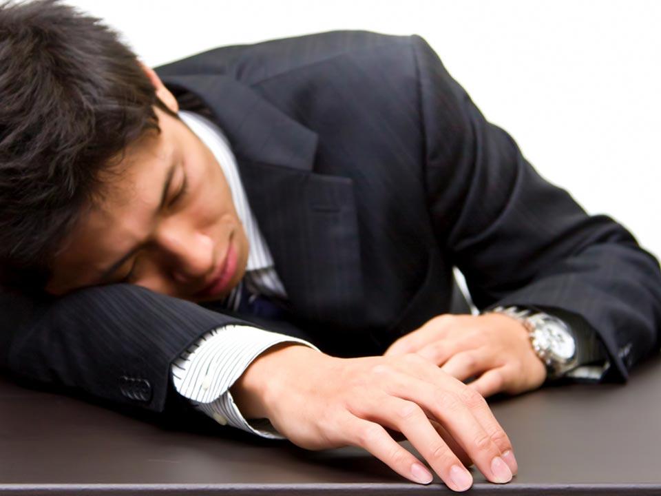 疲れて机で眠るビジネスマン
