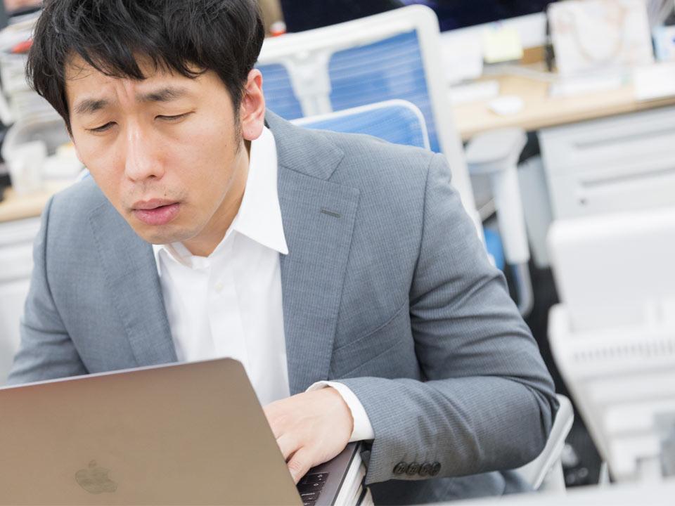 自信なさそうにパソコンを触る男性